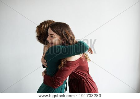 Best girl friends meet together after many years. Stylish woman embrace on neutral background. Friendship concept. Two female in green and red suit. Happy and smiling emotions after fun time.