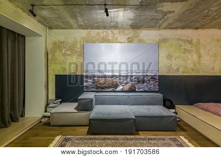 Room in a loft style with shabby walls and a parquet with a carpet on the floor. There are sofas with a big photo over them, luminous, lamps, wooden lockers, piles of books, speaker, curtains.