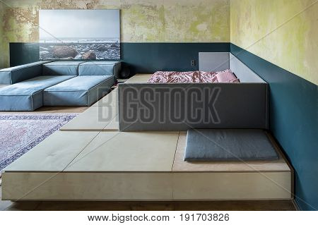 Stylish bedroom in a loft style with shabby walls and a parquet with a carpet on the floor. There are sofas, large wooden bed with rose linens and pillows, big photo on the wall. Horizontal.