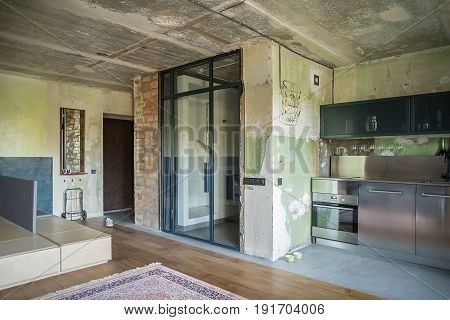 Studio in a lost style with shabby and brick walls. There is a bathroom zone with glass doors with curtain and a shower, kitchen zone with oven, sink, chrome steel lockers and reticulated shelves.
