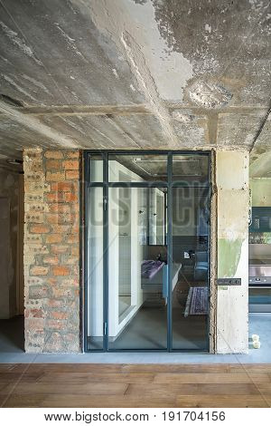 Bathroom zone with a glass door in the interior in a loft style with shabby and brick walls. There is a white tiled shower, sink with a mirror, toilet. On the right there is a kitchen zone. Vertical.