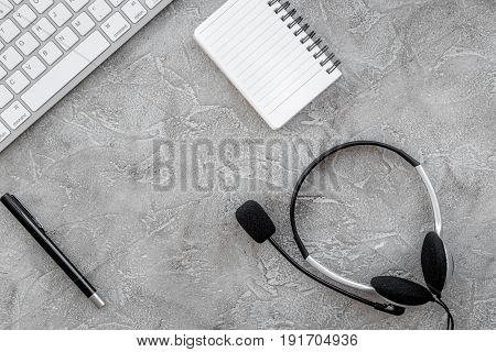 call center manager work place with headset and notebook on stone desk background top view mock up