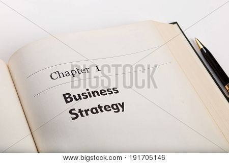 chapter one in an open book with a pen business strategy. fake book.