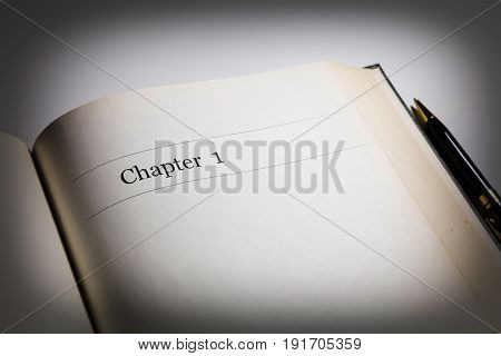 chapter one in an open book with a pen