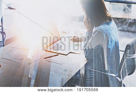 Businesswoman working process at modern office.Account manager work wooden table with paper documents and mobile laptop.Double exposure, skyscraper building blurred background.Horizontal.Flares effect