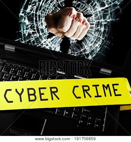 Hacker fist on laptop screen with cyber crime police tape