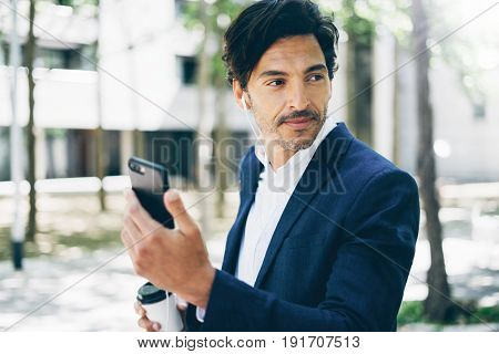 Closeup view of h andsome smiling businessman using smartphone for listining music while walking in city park.Horizontal, blurred background