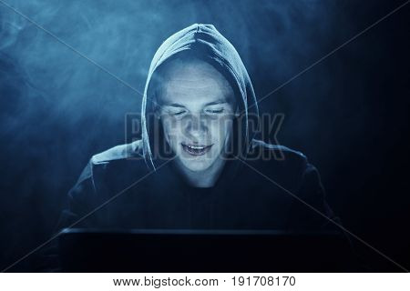 Hacker in a hood in a smoggy background.