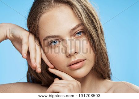 Woman touched her face with her hands on a blue background portrait.
