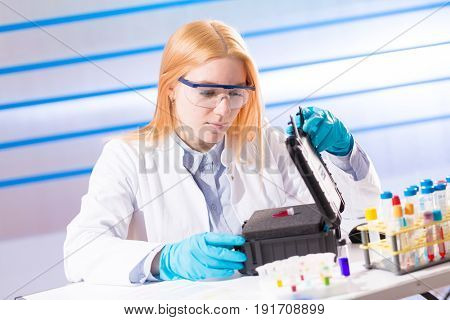 Female laboratory assistant with blood test for AIDS