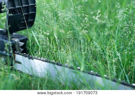 Electric saw on grass with blurred background