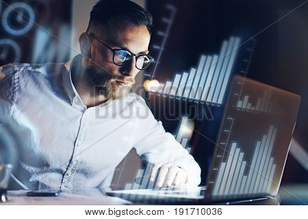 Concept of digital diagram, graph interfaces, virtual screen, connections icon.Young entrepreneur working at modern office on laptop.Man using digital touch pad at night, blurred background.Horizontal