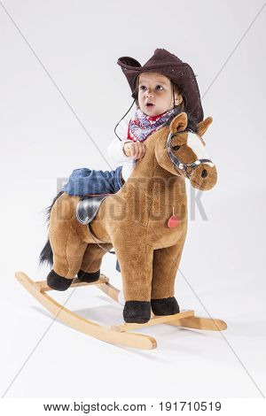 Children Consepts. Little Caucasian Girl Posing in Cowgirl Clothing with Toy Horse Against White Background.Vertical Image Composition