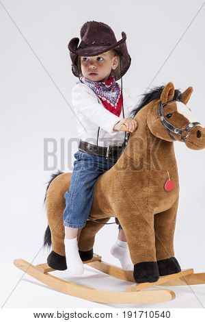 Children Consepts. Assured Calm Little Caucasian Girl in Cowgirl Clothing On Symbolic Horse Against White Background. Vertical Image Composition