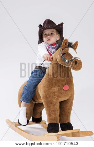 Playful Caucasian Little Girl in Cowgirl Clothing On Symbolic Horse Against White Background. Vertical Image Composition