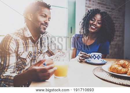 Happy african american couple are having breakfast together in the morning at the wooden table.Young black man and his girlfriend drinking fresh juice and black coffee on breakfast at at home.Flares