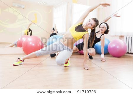 Sport Fitness Healthy Lifestyle Concepts.Two Female Caucasian Athletes in Good Fit Having Arms Stretching Exercises in Sport Gym.Horizontal Image