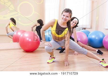 Sport Fitness Healthy Lifestyle Concepts.Two Female Caucasian Athletes in Good Fit Posing With Fitballs in Sport Gym.Horizontal Image