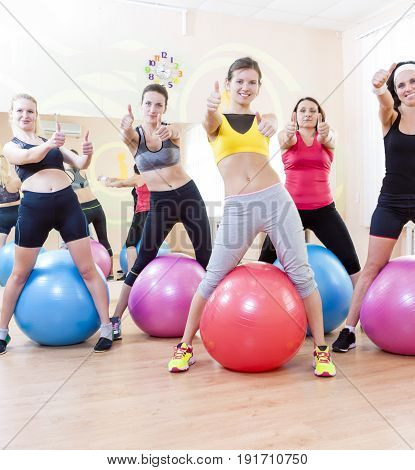 Sport and Fitness Concepts and Ideas. Group of Five Caucasian Female Athletes Having Exercises With Fitballs in Gym and Showing Thumbs Up Sign. Vertical Image Orientation