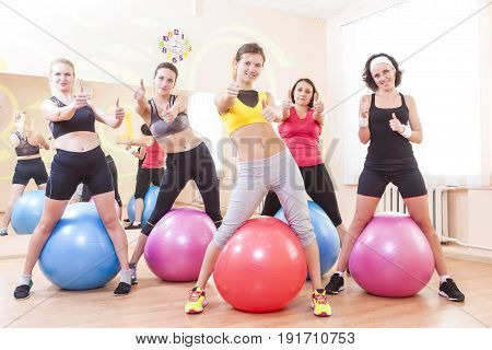 Sport and Fitness Concepts. Group of Five Caucasian Female Athletes Having Exercises With Fitballs in Gym and Showing Thumbs Up Sign. Horizontal Image Orientation