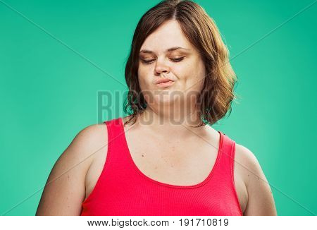 Woman looking down, fat woman curled her lips against a green background portrait.