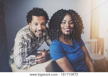 Happy young black african couple moving boxes into new apartment together and making a beautiful life.Cheerful family sitting in empty new home.Horizontal.Blurred background.Cropped.Flares