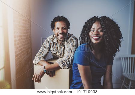 Happy young black african couple moving boxes into new apartment together and making a successful life.Cheerful family sitting in empty new home.Horizontal.Blurred background.Flares