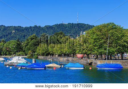 Zurich, Switzerland - 18 June, 2017: embankment of Lake Zurich in the city of Zurich, boats on the lake, Mt. Uetliberg in the background. Lake Zurich is a lake in Switzerland, extending southeast of the city of Zurich.