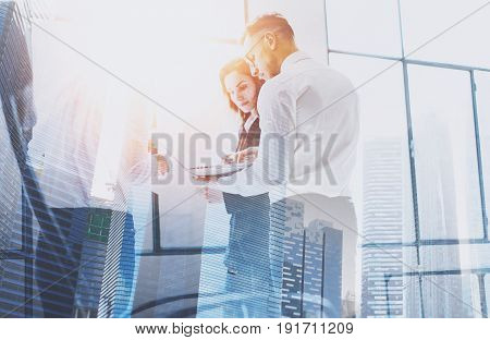 Group of businessmans on business meeting.Business team in working process.Double exposure, skyscraper building blurred background.Flares effect