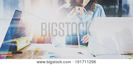 Young businesswoman working process at modern office.Account manager working at the wooden table with paper documents.Double exposure, skyscraper building blurred background.Wide, flares effect