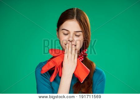 Woman yawning, woman holding red gloves on green background.