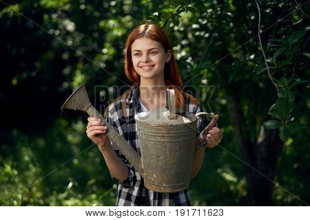 Woman in vegetable garden, young woman with watering can, woman watering grass.