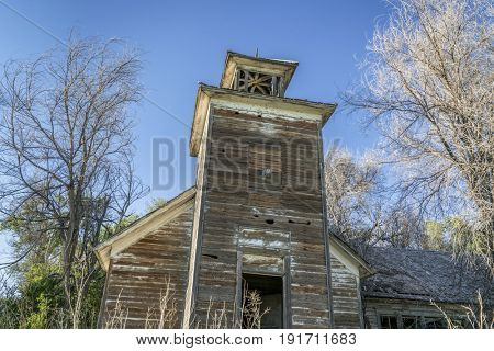 old abandoned schoolhouse with a bell tower in rural Nebraska overgrown by trees and weeds