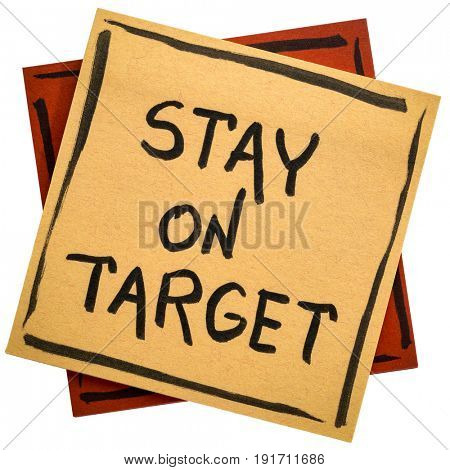 Stay on target - handwriting in black ink on an isolated sticky note