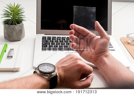 Augmented reality concept. Close-up of modern transparent smartphone being in hand of young man. Laptop with office things on the background
