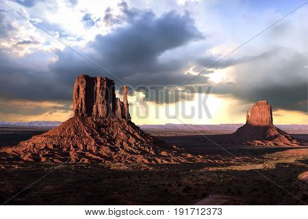 Beautiful dramatic sunset over the West and East Mitten Buttes in Monument Valley. Utah, USA
