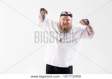 Angry male fat hipster is raising his arms with fists forward. He is standing and looking at camera with irritation. Man is showing tattoo on his fingers. Isolated and copy space in left side