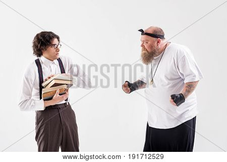 What did you say. Irritated thick male hipster is standing with his fists in front of scared victim. Boy in eyeglasses is holding books and looking at man with anxiety. Isolated