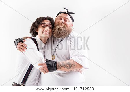 Friends forever. Happy fat male hipster and weak outcast are hugging with friendship. They are standing and smiling with closed eyes. Isolated and copy space in right side