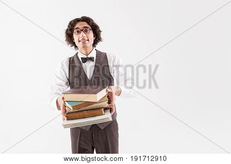 Read with me. Portrait of innocent clever young boy stretching books forward. He is standing and looking at camera with hope. Isolated and copy space in right side