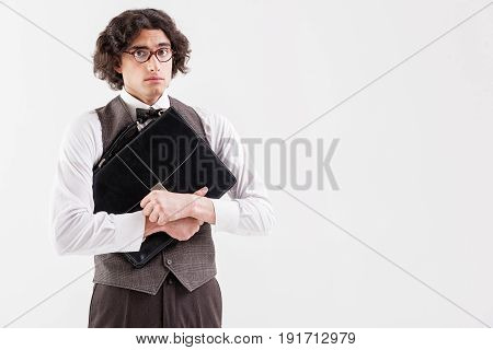 Abused young smart man is standing and hugging his briefcase. He is looking forward with sadness. Isolated and copy space