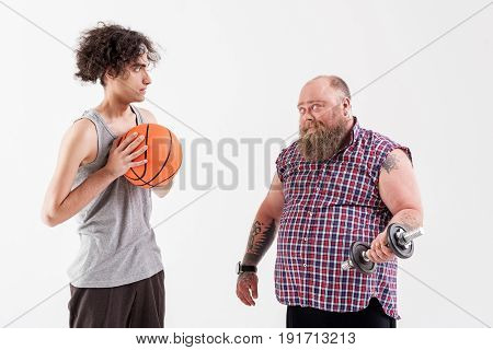 Look how I can. Confident fat bearded man is lifting dumbbell. Slim young boy is holding basketball ball and looking at fatso with fear. Isolated