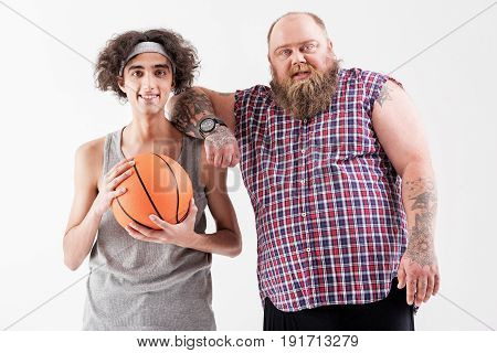 Together we are strength. Portrait of confident thick bearded man leaning on shoulder of slim boy friendly. Weak guy is holding ball and smiling. Isolated