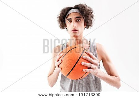 Frightened thin boy is standing and holding ball. He is looking at camera with fear. Isolated and copy space in left side. Portrait