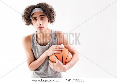 Waist up portrait of skinny young man carrying ball and looking forward with anxiety. Isolated and copy space