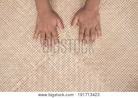 Children hand on basketry bamboo background .