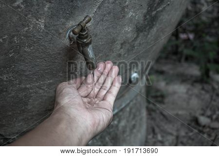 Asian boy open metal water faucet empty land. Water shortage concept.