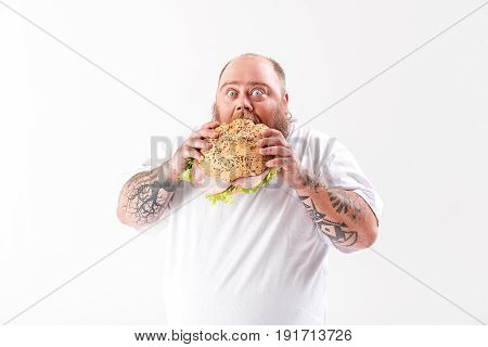 Ravenous male fatso is eating big bun with meat. He is standing and staring at camera with shock. Isolated