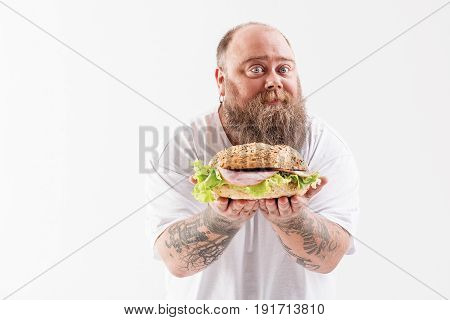 Joyful male fatso is presenting big hamburger with proud. He is standing and smiling. Isolated and copy space in left side