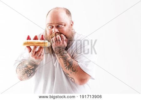 I want to eat it right now. Hungry male fatty is holding sweet cake and looking at it with appetite. He is standing and keeping fingers in mouth. Isolated and copy space